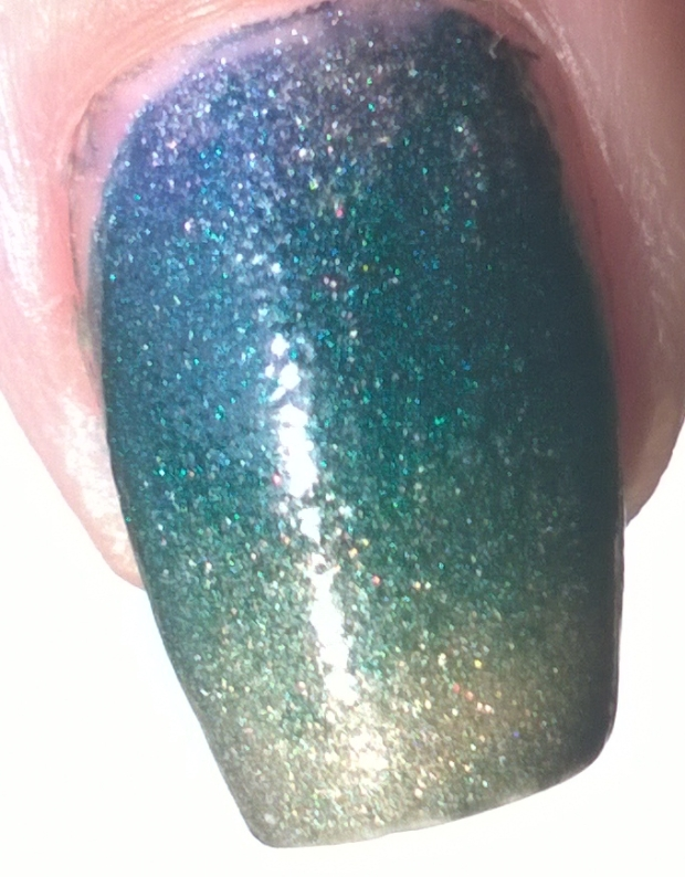 "Close up of my thumb to try and show the glimmer. There isn't as much as the polishes would have if applied normally but you can still get the copper from ""Dragon"" showing through"