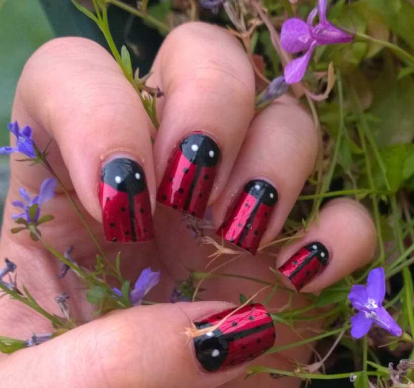 """Day 18: Half Moons. I hate half moon manicures usually but this is actually my favourite so far of the challenge. So proud of my ladybirds! The gorgeous red is A England """"Perceval"""" and the black detailing was done with a Models Own nail art pen. The eyes were dotted on with a Barry M nail art pen. Definitely going to recreate this one in the near future. Got tons of compliments at work too!"""