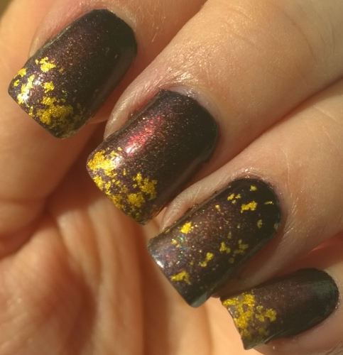 "Day 8: Metallic. I went with the literal version for this, the gold flakes are Cirque Color's ""AU"" - 22k gold flakes. The gradient beneath is 2 gorgeous A England shades and 1 OPI shade. I tried to show the holographic effect but my camera just didn't want to pick it up. Definitely one I'll recreate."